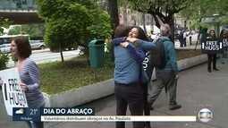 Voluntários distribuem abraços na Avenida Paulsita para comemorar Dia do Abraço