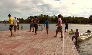 Meninos driblam cheia de rio no AM e jogam futebol em quadra flutuante