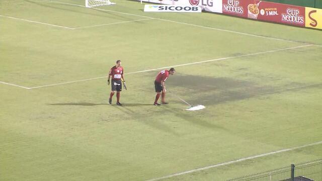 Trio de arbitragem ajuda a retirar a água de campo na Arena Condá, e torcida aplaude