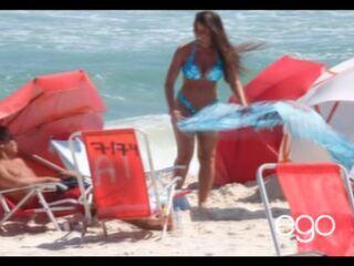 Nada de marquinhas! Nicole Bahls desamarra o sutiã do biquíni na praia