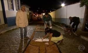 Voluntários viram a noite preparando tapetes de serragem para Corpus Christi