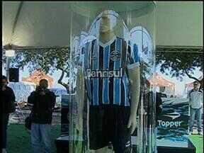 Grêmio lança a nova camisa da temporada 2013 - A camisa tricolor tem detalhes em branco na gola e nas mangas, e a segunda camisa é toda branca com listras em azul e preto nas mangas e gola.