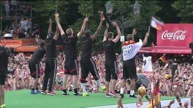 Jogadores da Alemanha comemoram o tetracampeonato em Berlim - Milhares de pessoas lotaram o Portão de Brandemburgo. Os atletas subiram num palco para exibir a taça do mundial. Torcedores acompanharam a seleção no caminho do aeroporto ao portão em carro aberto.
