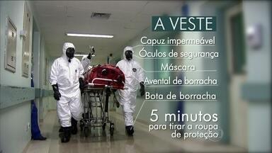 Equipe hospitalar usa roupa de proteção de borracha impermeável para prevenir o ebola - O africano, de 47 anos, está internado no Instituto Evandro Chagas, hospital de referência nacional para casos de ebola no Brasil. A equipe segue protocolo de segurança e isolamento.