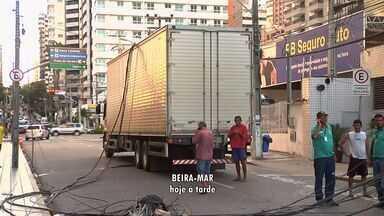 Caminhão arrasta fiação e derruba postes em Fortaleza - Um dos postes caiu sobre veículo de uma senhora, que não se feriu.