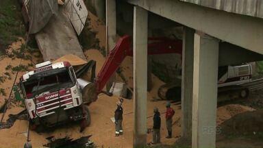 Bitrem carregado de milho cai de viaduto na BR-376 - O veículo foi parar na linha do trem. O motorista teve ferimentos graves.