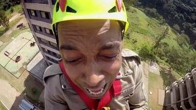 Hoje é dia de bombeiro: salvamento em altura - Alexandre Henderson encara o desafio de descer de tirolesa, simulando uma ação de resgate do nono andar de um prédio, a 30 metros de altura .