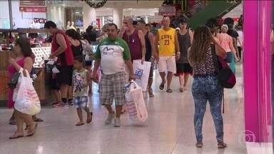 Shoppings ficam cheios para os presentes de última hora - Mesmo com crise e falta de tempo, há o esforço para presentear. Para ganhar tempo, pai leva o presente do filho sem embrulhar.