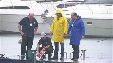 Peritos resgatam gravador de voz do avião que caiu em Paraty - Bombeiros e mergulhadores trabalham para tirar o avião do mar. Testemunhas dizem que avião voava baixo e parecia querer voltar.