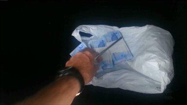 Vídeo mostra policiais recuperando dinheiro em forro de veículo - O dinheiro teria sido resultado de roubo em banco.