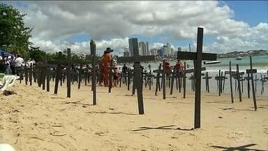 Manifestantes protestam contra o aumento da violência em Natal - Mil cruzes pretas, simbolizando um cemitério, foram colocadas na praia de Ponta Negra, perto do Morro do Careca, o principal cartão postal da cidade. De janeiro até agora, 1,1 mil pessoas foram assassinadas no estado.