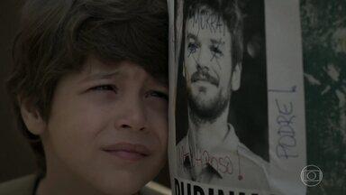 Dedé sofre por causa de Rubinho - O menino vê um cartaz com a foto do pai como foragido da polícia