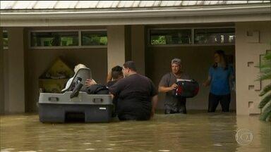 Moradores de Houston usam barcos para tentar resgatar pertences - Prefeito decretou toque de recolher para evitar saques nas casas alagadas. Texas tem pelo menos 49 mil casas alagadas, e 32 mil pessoas estão em abrigos.