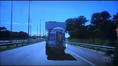 Carro é flagrado transportando carga acima do permitido, em Goiânia - Motorista carrega um armário no teto do veículo. Porta de trás também está aberta.