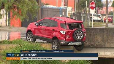 Acidentes envolvendo ônibus e carros são registrados em Curitiba - Em uma das batidas, o carro ficou pendurado no rio.