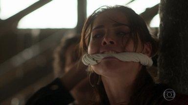 Laureta avisa Karola que a polícia está na região - Laureta pede pra Karola ouvir seu plano. Karola vai até Rosa e amarra sua boca.