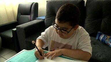 Família de menino com doença degenerativa vende canecas com desenhos para o tratamento - João Gabriel é quem faz os desenhos.