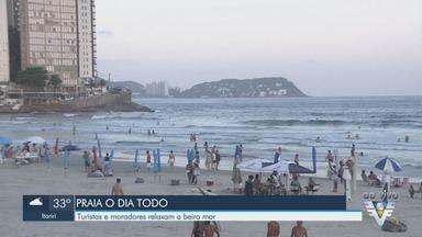 Calor leva banhistas até a praia de Pitangueiras em Guarujá, SP - No começo de noite, muitas pessoas estão na praia.