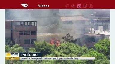 Moradores tentam apagar incêndio em vegetação com balde de água, na Serra - O Corpo de Bombeiros foi chamado e e conseguiu controlar as chamas.