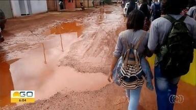 Alunos protegem os pés com sacolas para chegar em escola sem sujar sapatos, em Cristalina - Prefeitura havia prometido asfaltar a rua, mas promessa ainda não foi cumprida.