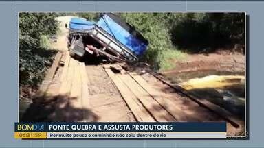 Ponte quebra e caminhão fica pendurado - Parte da carga de milho foi levada pelo rio.