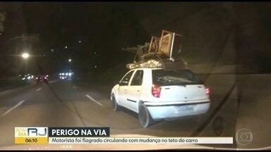 Motorista é flagrado circulando com mudança no teto do carro no Rio - O carro circulava pelo túnel Rebouças carregando móveis no teto.