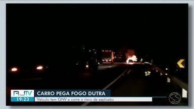 Carro pega fogo e interdita Via Dutra, em Itatiaia - Segundo PRF, veículo é equipado com GNV e corre risco de explosão. Suspeita é de que o incêndio tenha iniciado no motor do automóvel.