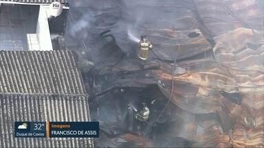Bombeiros continuam fazendo o rescaldo no galpão incendiado ontem (01), no Santo Cristo - A fumaça chama a atenção de longe. Homens do corpo de bombeiros continuam jogando água no galpão, na rua Pedro Alves, no Santo Cristo.