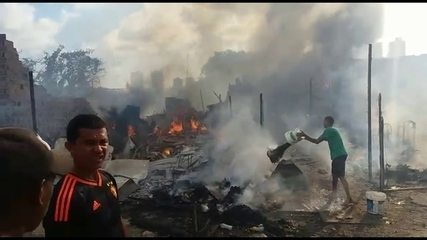 Moradores tentam apagar as chamas na comunidade Vila Santa Luzia, na Torre