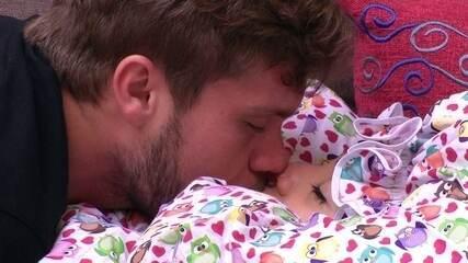 Breno e Paula trocam beijos no sofá da sala