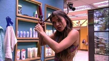 Paula alisa cabelo no banheiro da casa