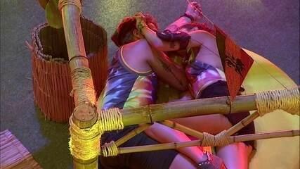 Paula e Breno trocam carinhos deitados em pufe