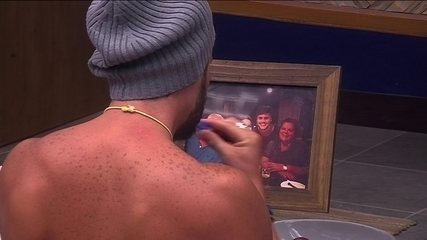 Breno escova os dentes olhando a foto da família