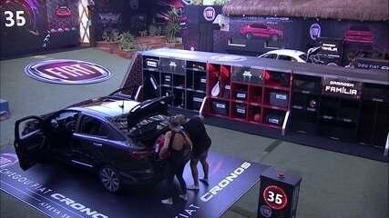 Kaysar e Jéssica colocam objetos no porta-mala do Fiat Cronos Vermelho Marsala