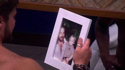 Breno observa foto de sua família no Bangalô do Líder