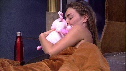 Paula beija porquinha de pelúcia e a coloca de volta na cama