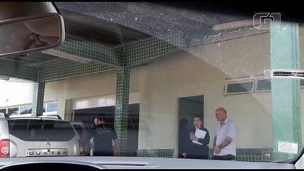 Um dos alvos da operação Conteiner ao ser colocado em automóvel da polícia