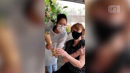 Idosa presenteia enfermeira com flores após receber dose da vacina contra a Covid-19