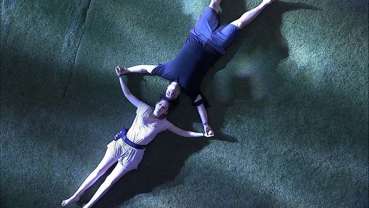 Ana Clara e Jorge deitam de mãos dadas no jardim