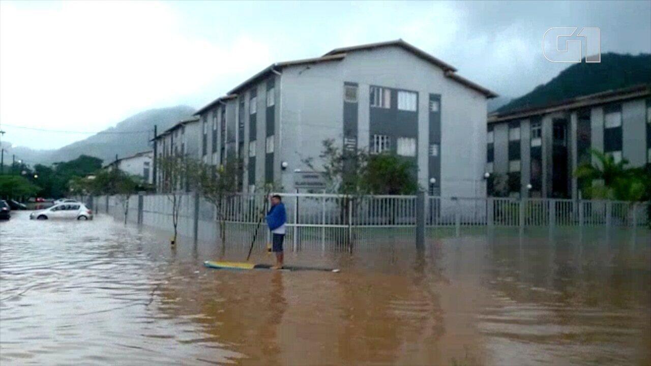 Morador improvisa stand up paddle em enchente em Ubatuba