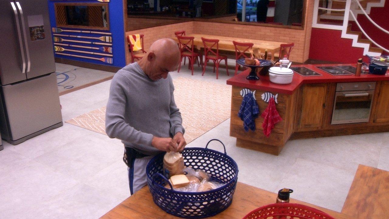Ayrton prepara sanduíche na cozinha