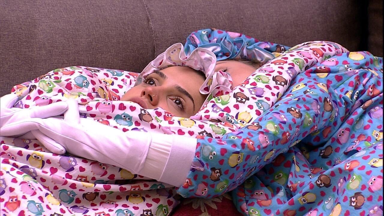 Paula fica pensativa deitada no sofá