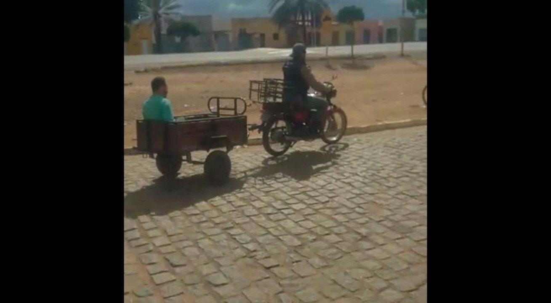 Polícia transporta suspeito de assalto em reboque de motocicleta