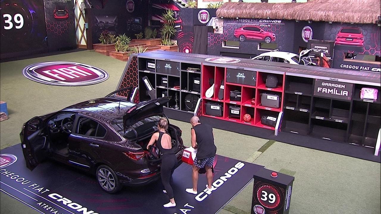 Jéssica e Kaysar movem itens para o porta-malas do Fiat Cronos Vermelho Marsala