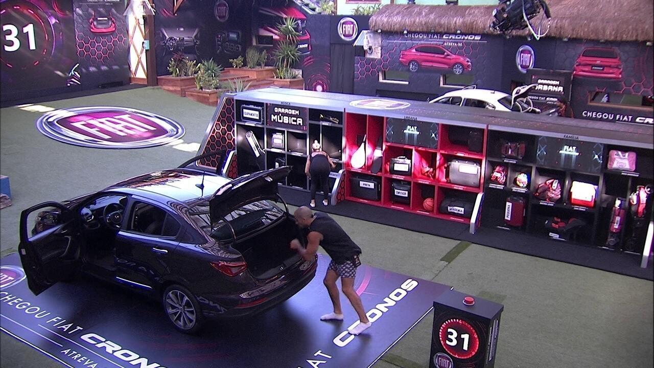 Kaysar e Jéssica retiram itens do bagageiro do Fiat Cronos Vermelho Marsala