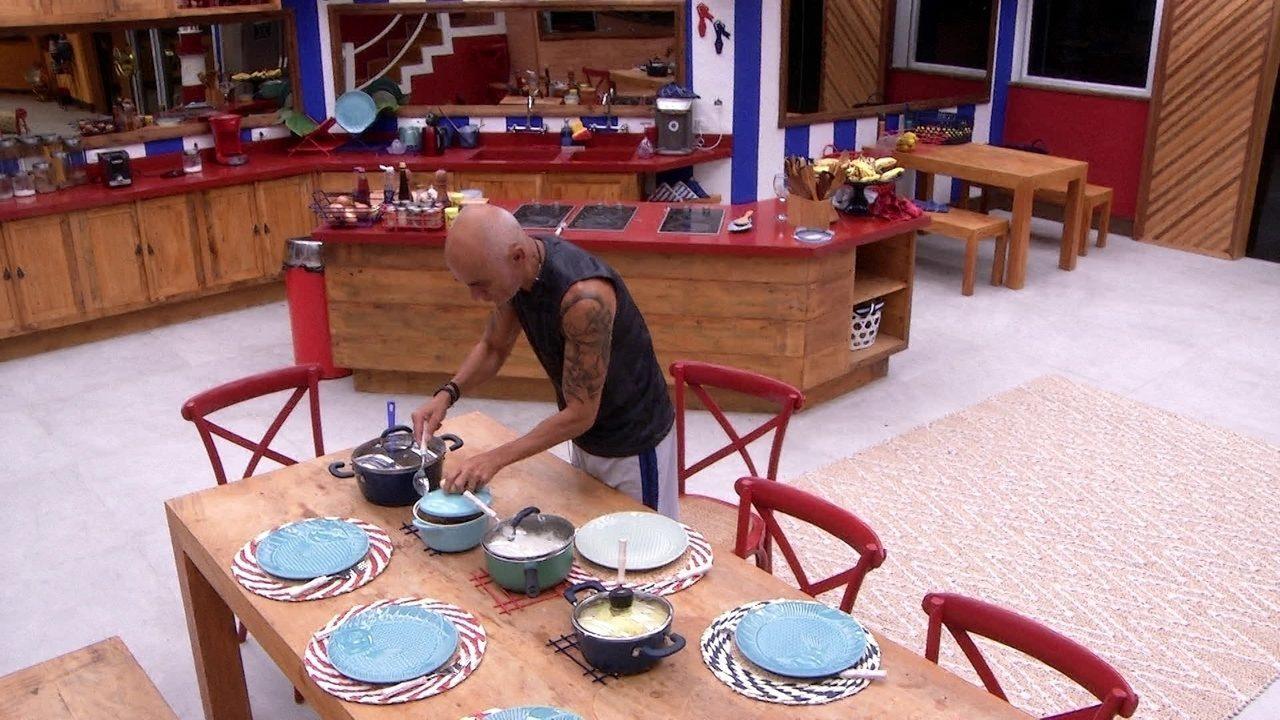 Ayrton mexe nas panelas de comida em cima da mesa