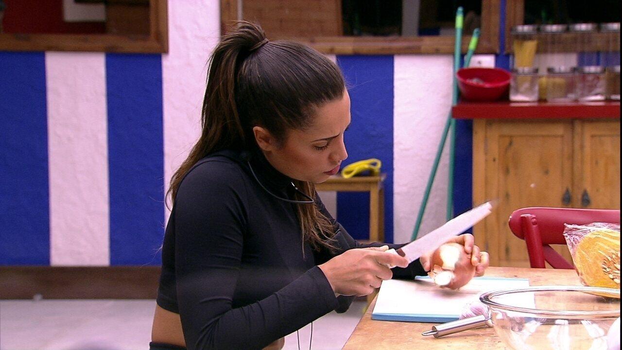 Paula descasca cebola na cozinha