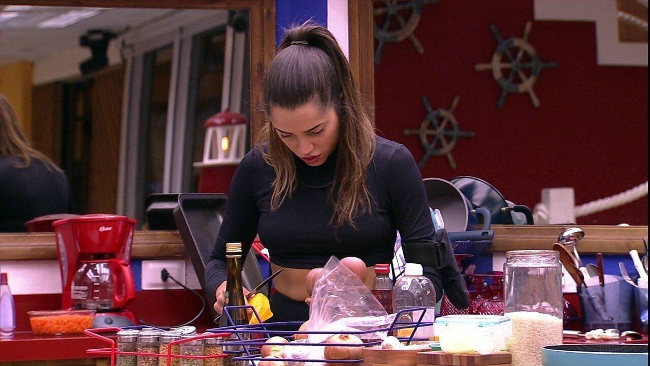Paula descasca abóbora na cozinha da casa