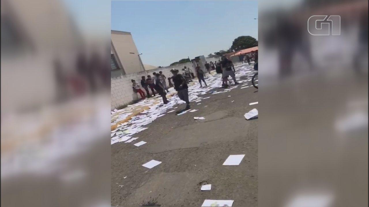 Estudantes rasgam apostilas em frente de escola para comemorar fim de ano