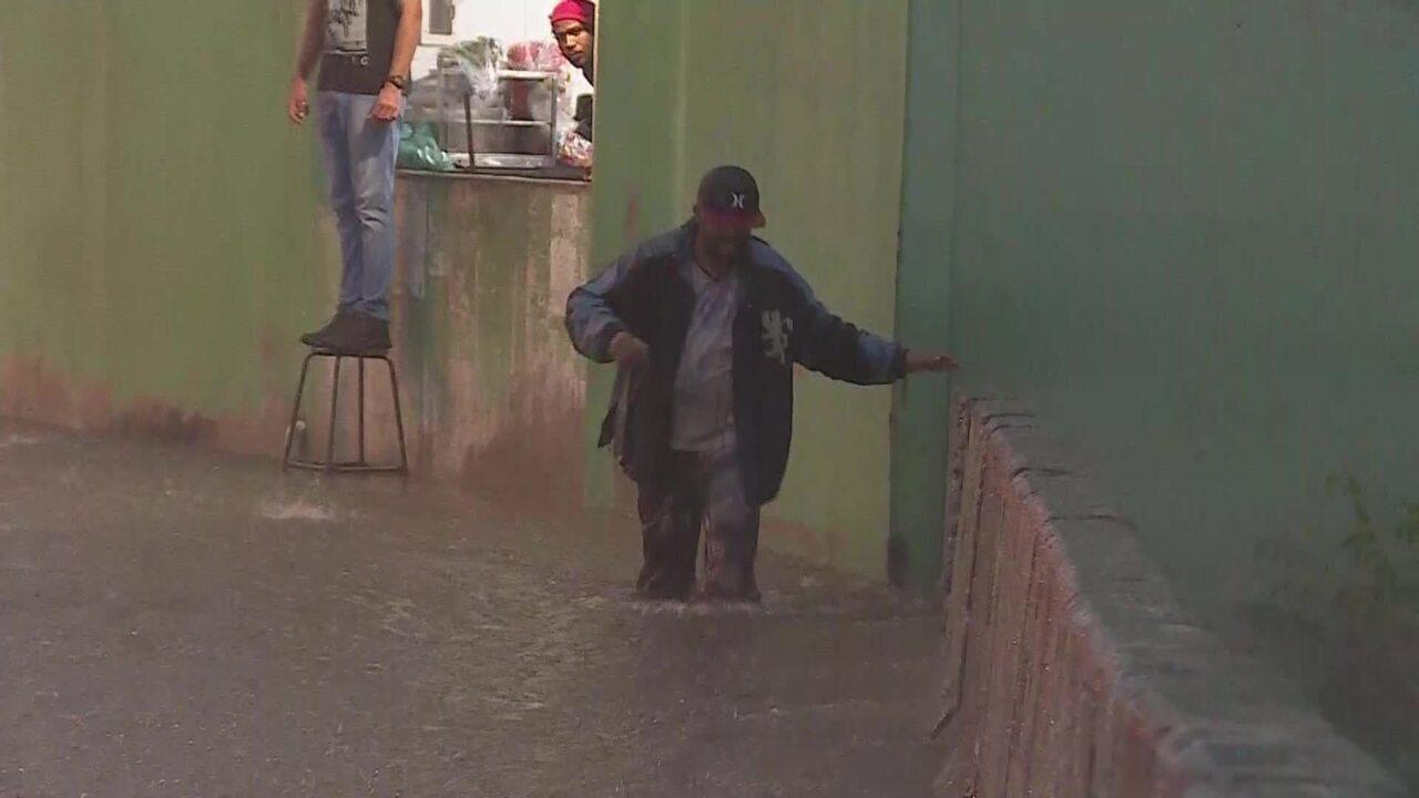 Pessoas se arriscam ao atravessar rua alagada em Belo Horizonte